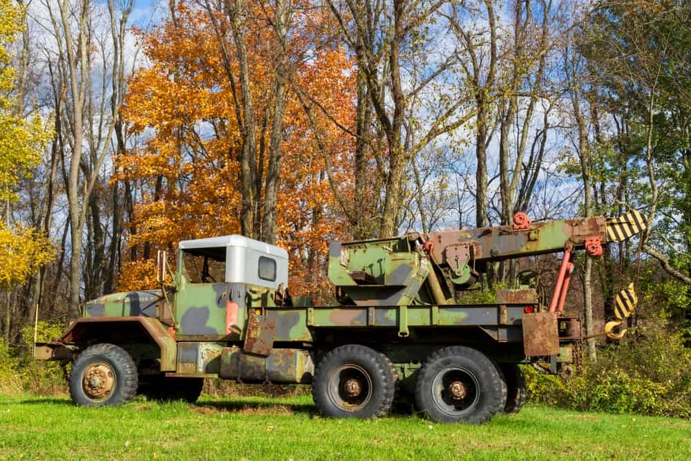 A military tow truck parked on grass.