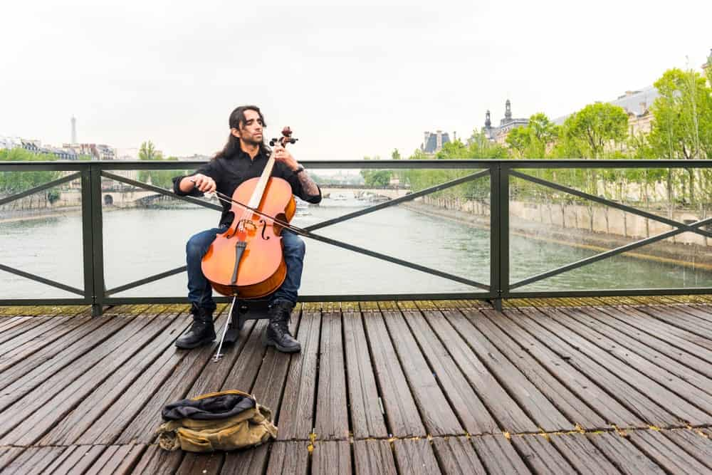 French cellist playing the cello on a bridge in France.