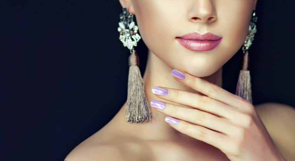 Woman with dangling earrings and colored nails wearing pearl lipstick.