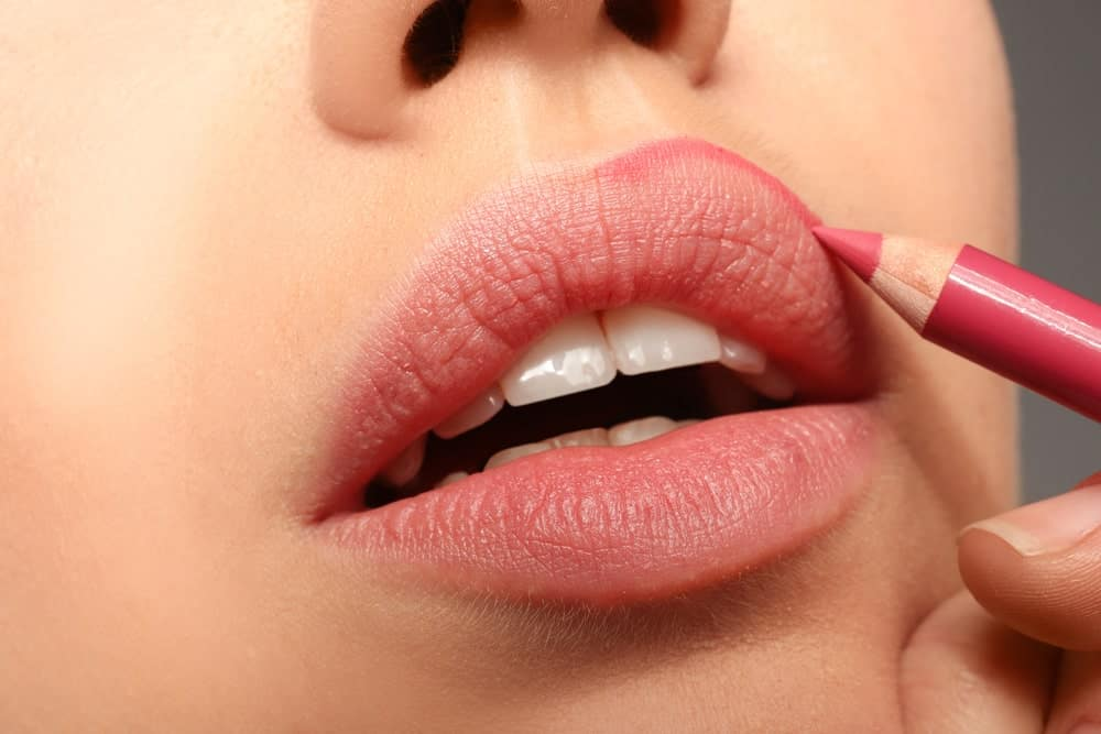 Woman applying lipstick pencil on her lips.
