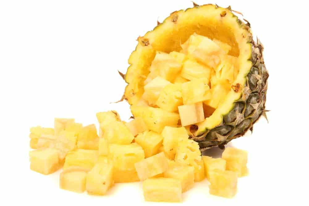 Pineapple chunks spilling from an empty half pineapple.