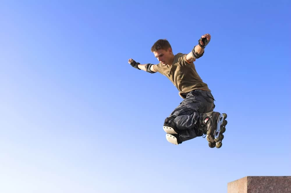 A young man wearing roller blades in the air.