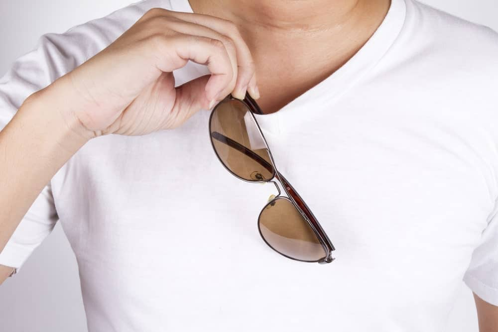 Closeup of a man putting on or removing his sunglasses on his round neck T-Shirt.