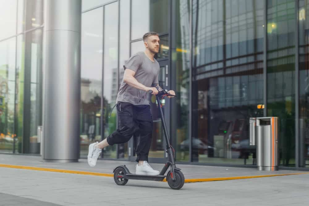 A man passes by a company building as he rides on his scooter.