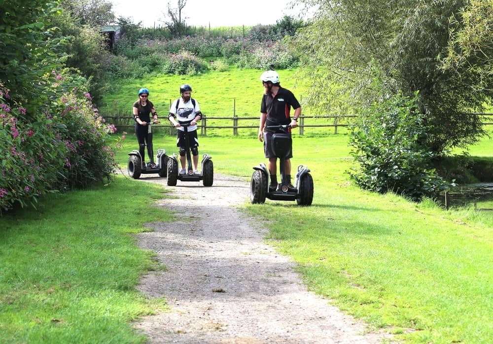 Three people riding on segway devices.