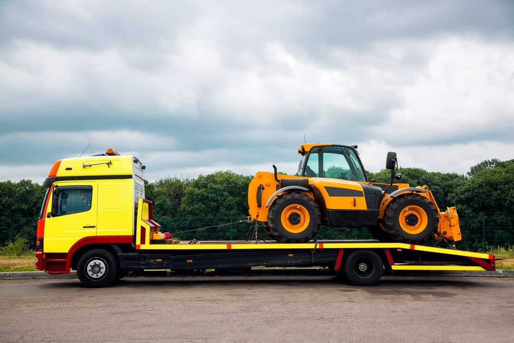 A flatbed tow truck transporting a new tractor.
