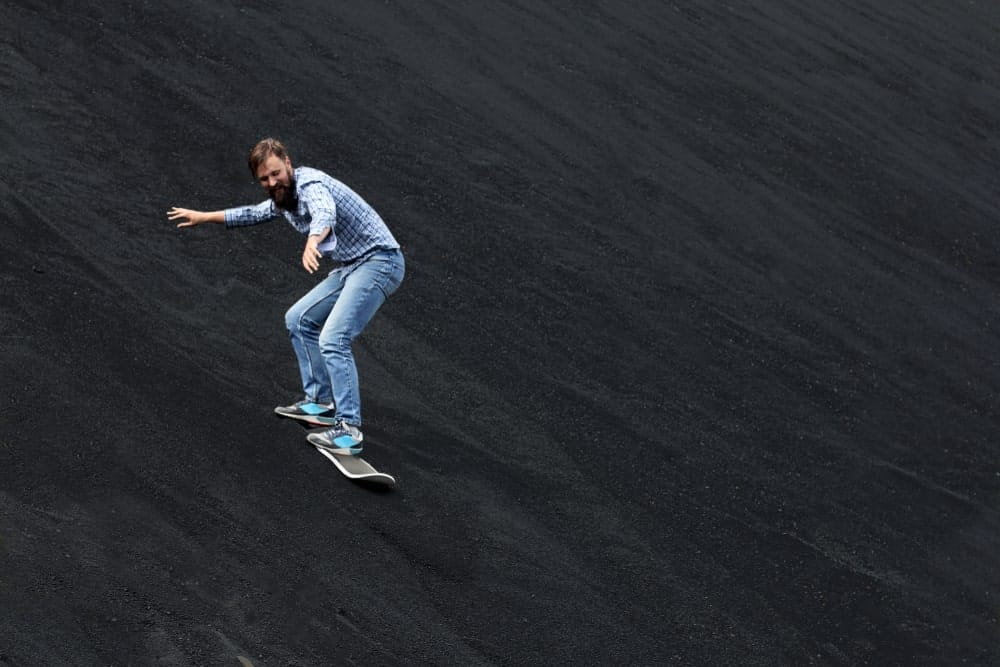 Man gliding down a black slope on snowskates.