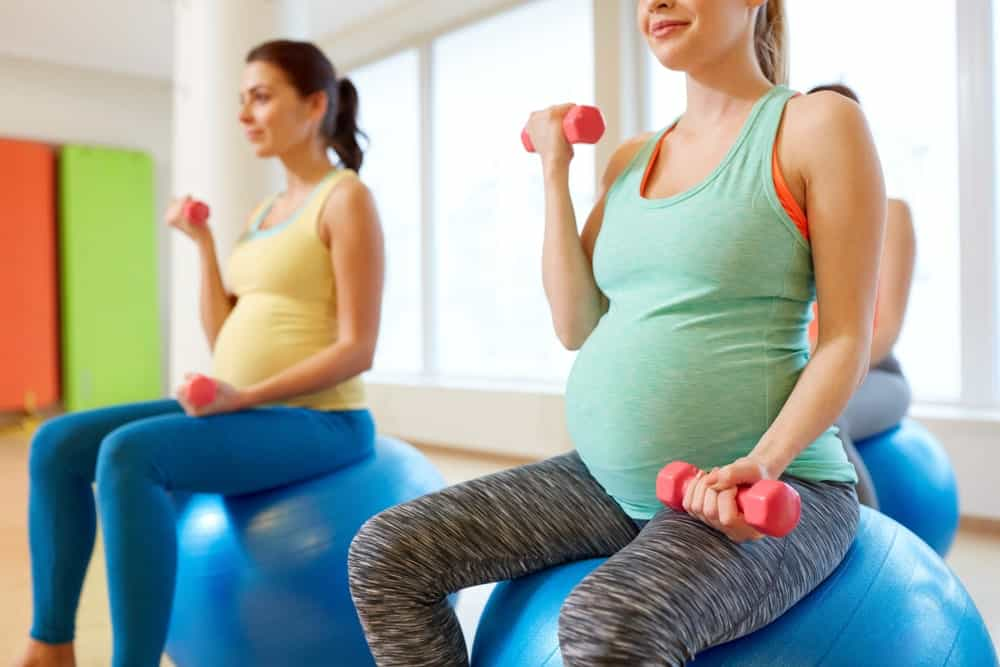 Pregnant women working out using dumbbells.