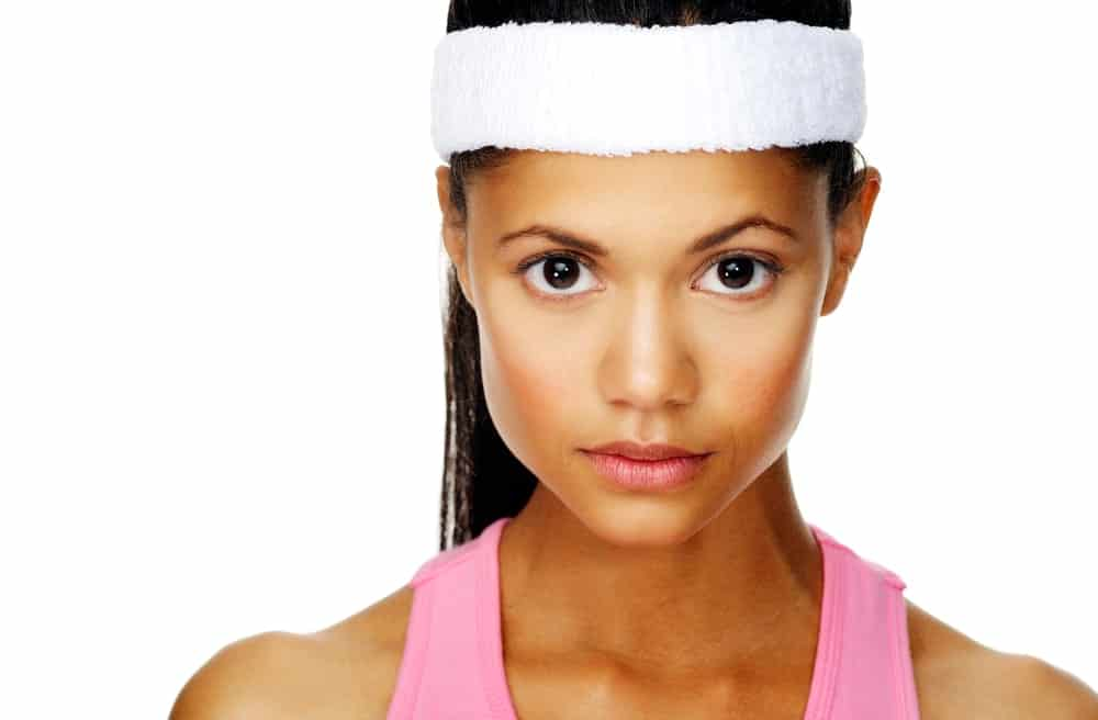Woman wearing a sweatband and tank top.