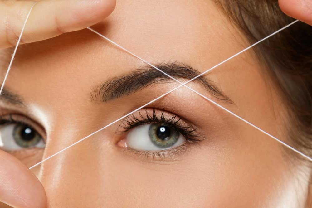 A woman holds a thread on her eyebrow for threading.
