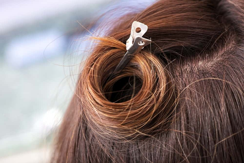 Hair tied in a curl using a metal hairpin.