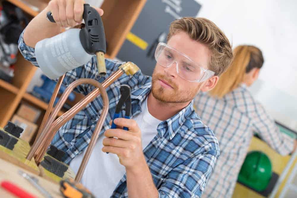 A young man wearing a pair of blowtorch goggles while working on a blowtorch.