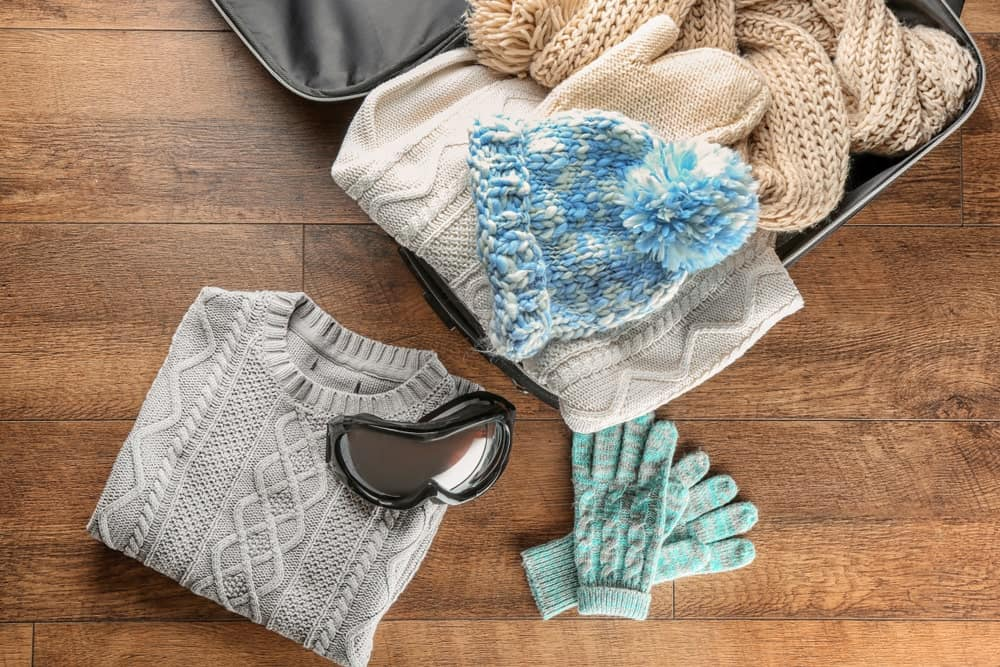 An open suitcase of knitted winter clothes and a winter sports goggles.