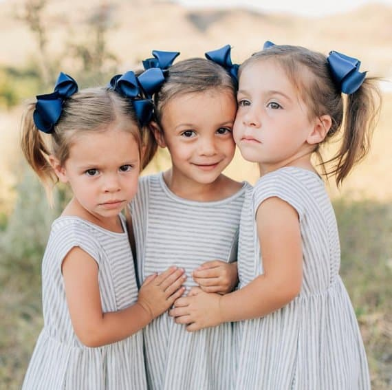 Three young girls wearing identical grosgrain bows and striped dresses.