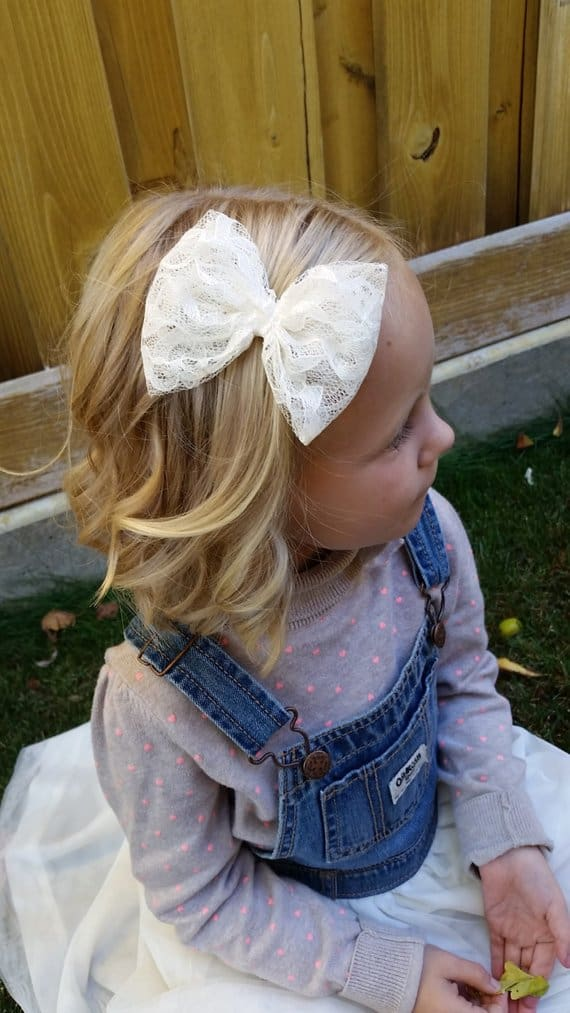 Top side view of a young girl wearing a lace bow.