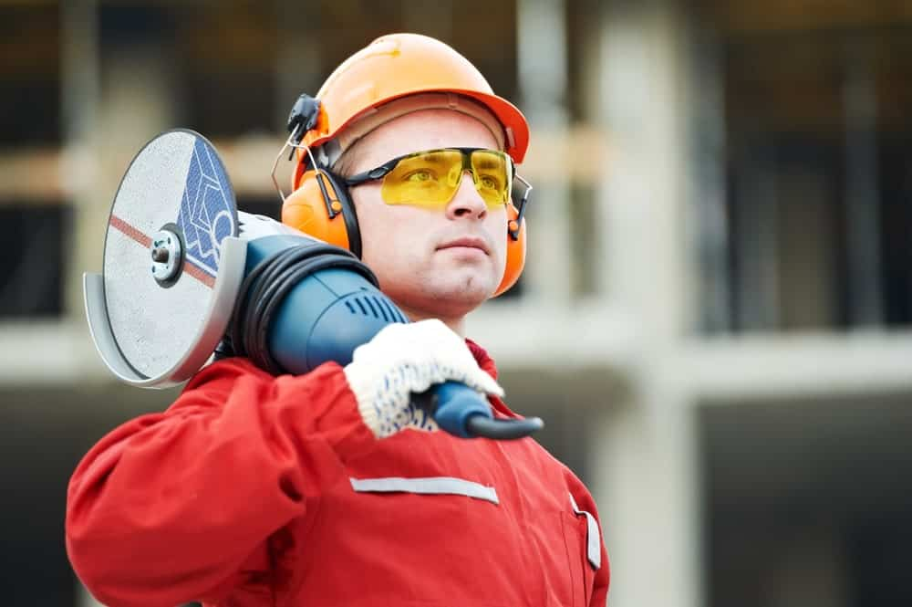 A construction worker wearing a complete suite of safety uniform including a pair of safety goggles holds a power grinder on his shoulder.