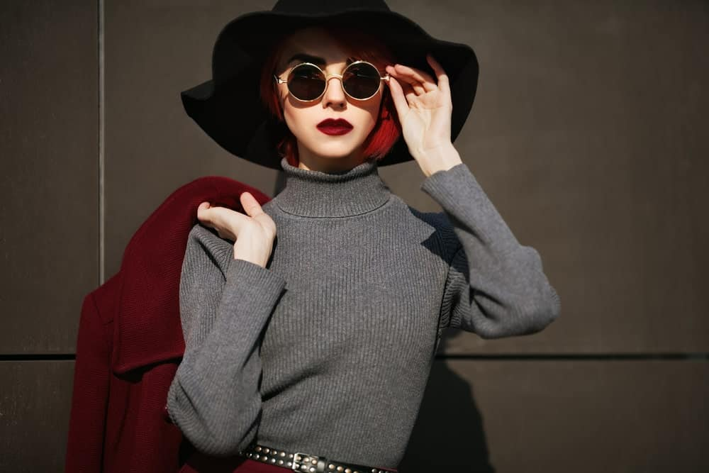 Stylish woman wearing a hat, shades, and a ribbed sweater while holding her red coat over her shoulder.