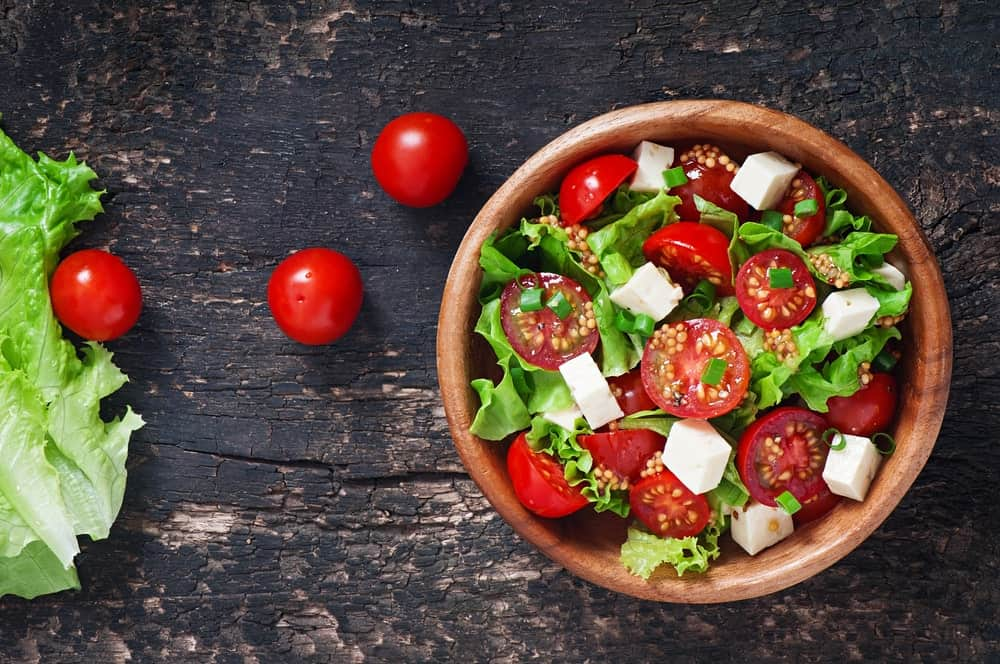 Salad tomatoes and a bowl of green salad with tomatoes.