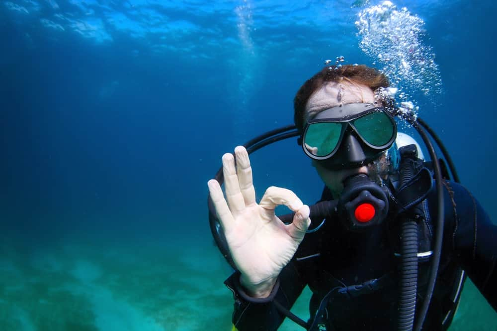 Scuba diver wearing a scuba diving goggles and suits makes an OK sign underwater.