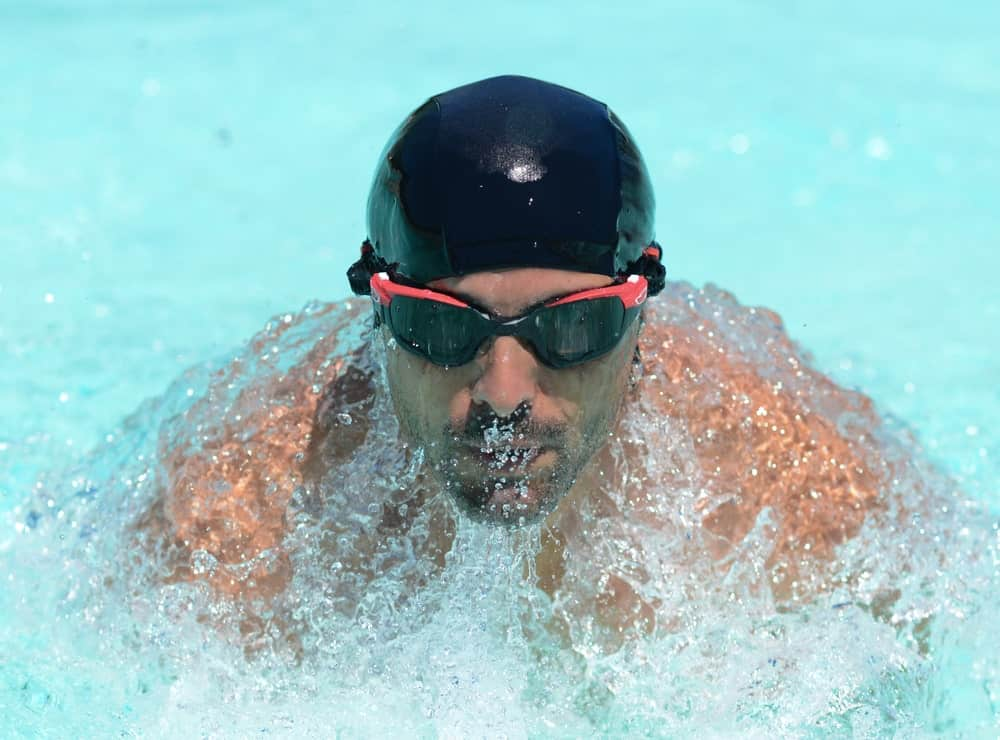 Swimmer wearing a swimming cap and swimming goggles rises out of the water as he breathes in for air.