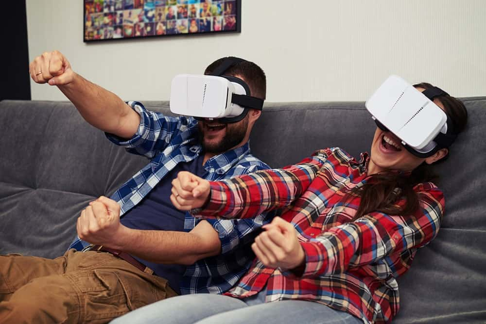 A man and a woman wearing virtual reality goggles and motioning as if driving a car.
