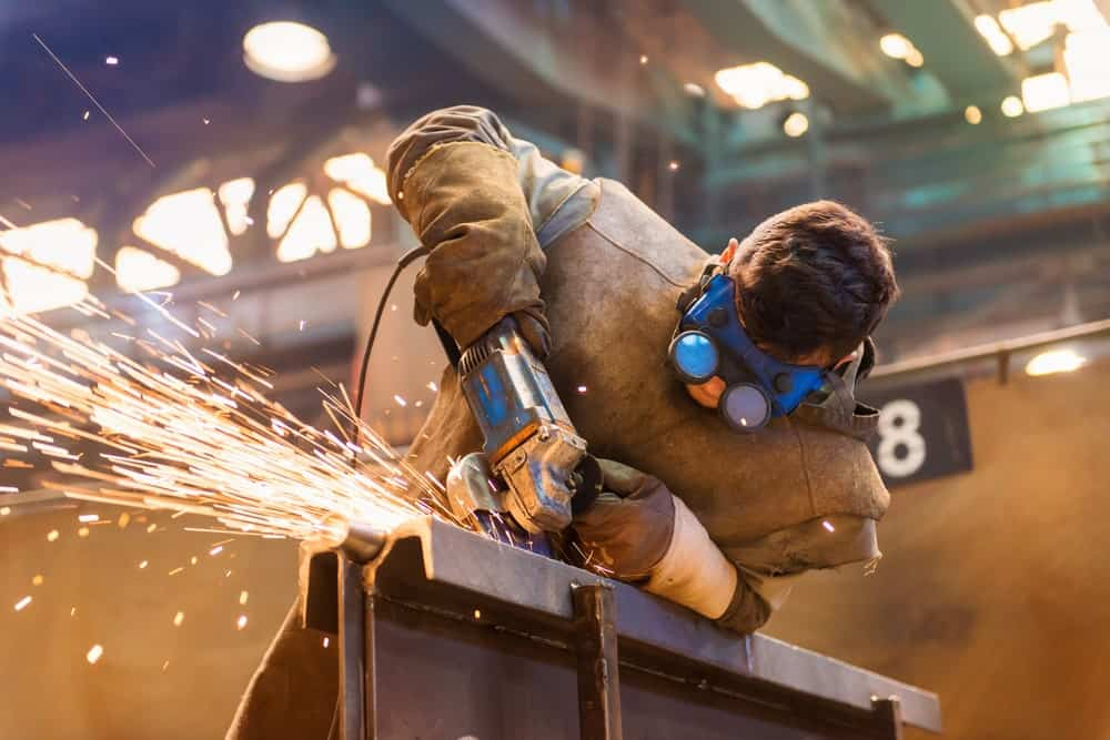 A welder at work wearing a pair of welding goggles.
