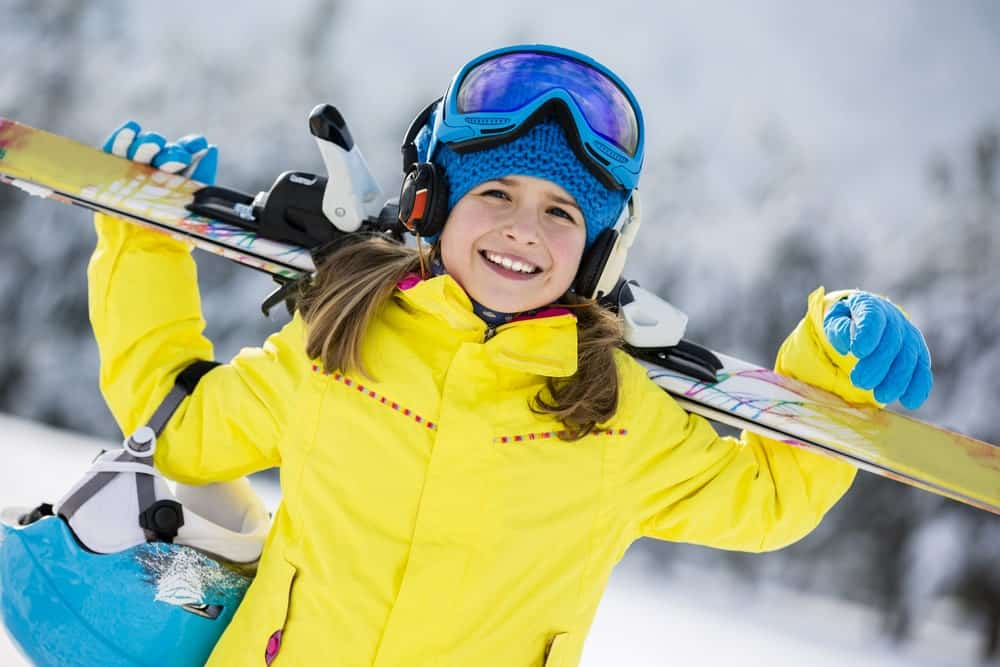 A young skier with a ski board on her shoulders.