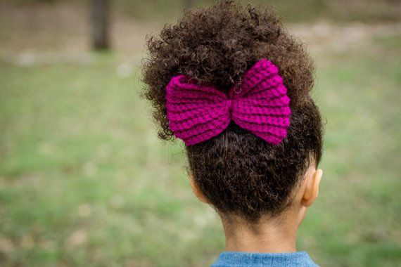 Back view of a young girl wearing a large yarn bow.