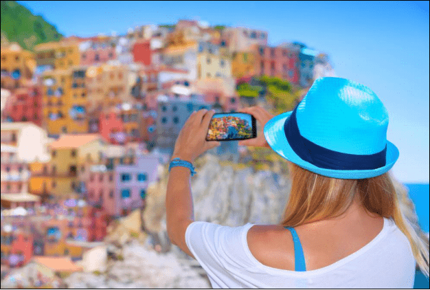 Woman Taking a Picture of Colorful Buildings