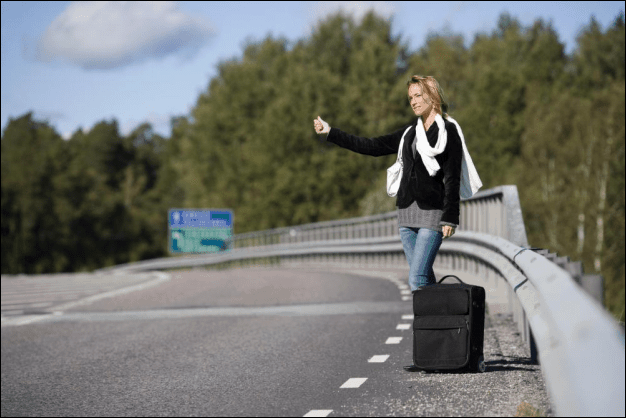 Young Hitchhiking Woman with a Travel Bag
