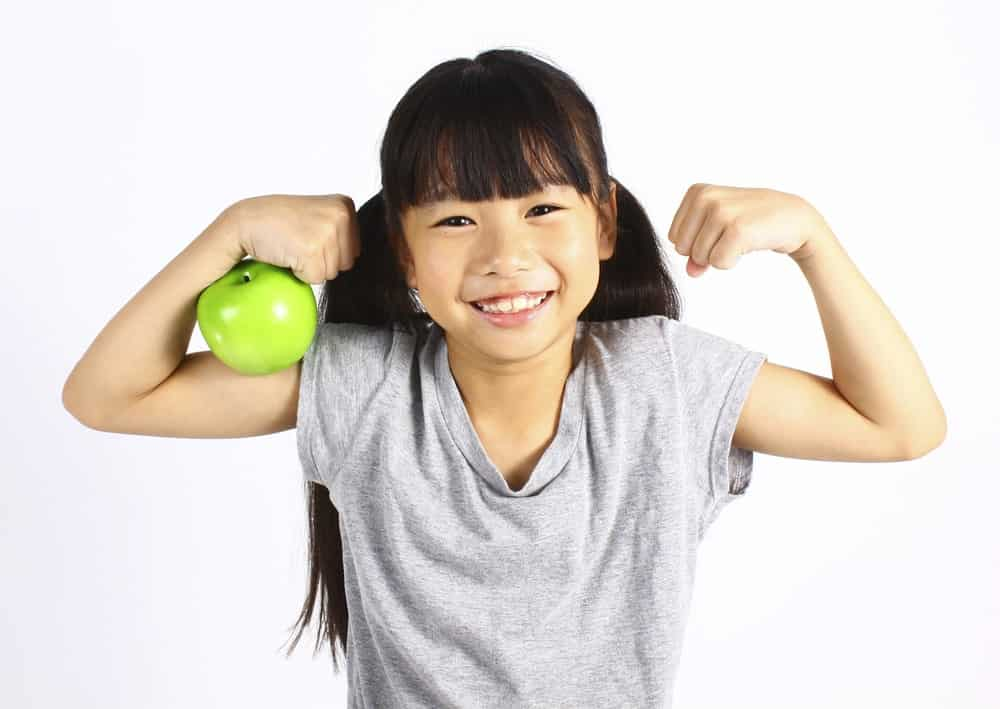 A girl flexing her muscles showing off an apple