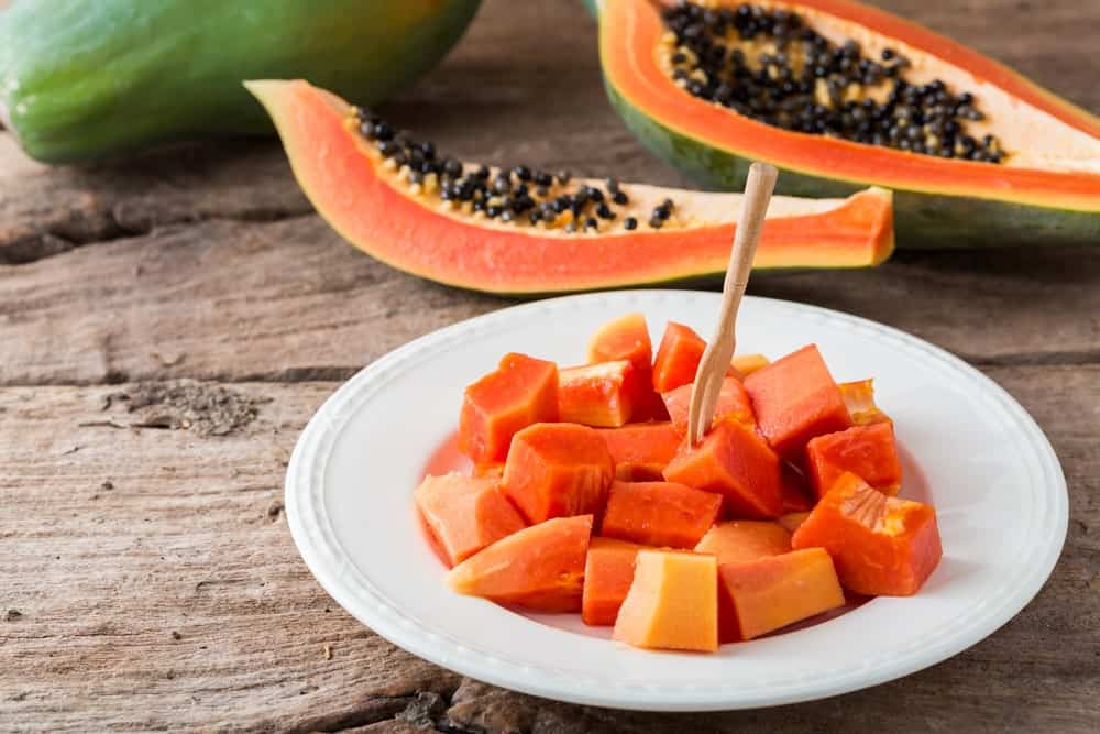 A whole papaya with sliced half pieces and chunks of papaya in a dessert platter.