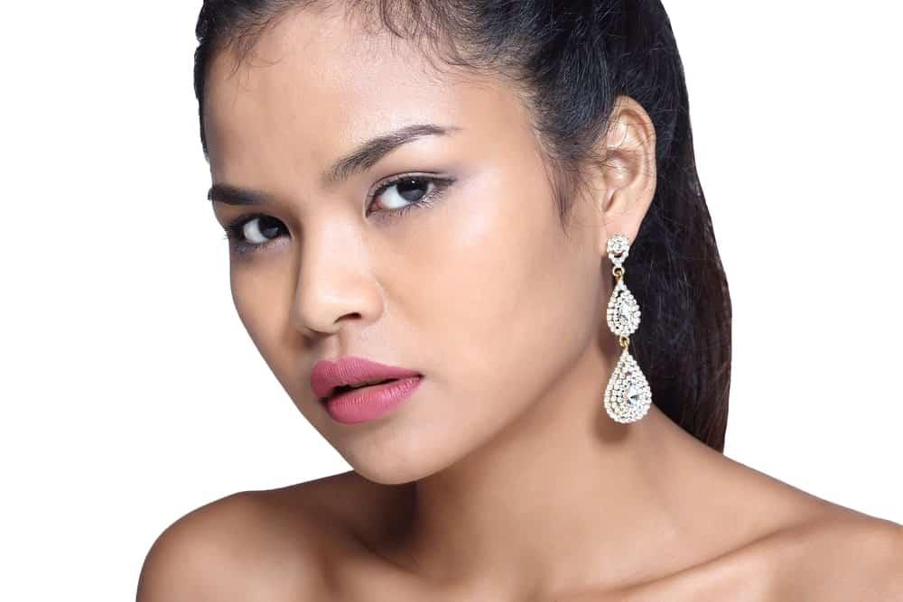 Woman wearing tear drop earrings.