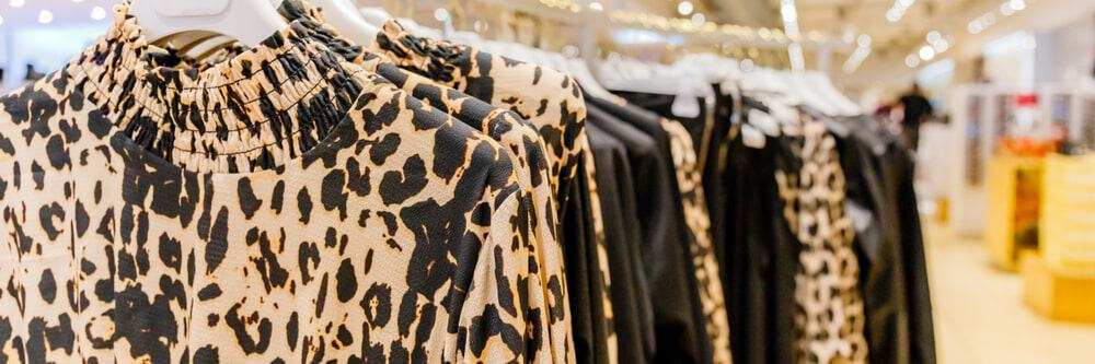 Store display of women's dresses with animal prints.