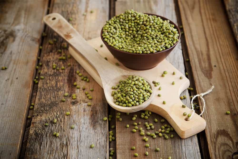 Green mung bean in a wooden bowl kept over a wooden board.
