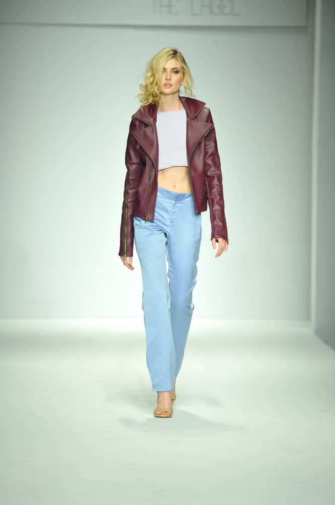 Model walking the rampway sporting a cropped jacket, top, and jeans.