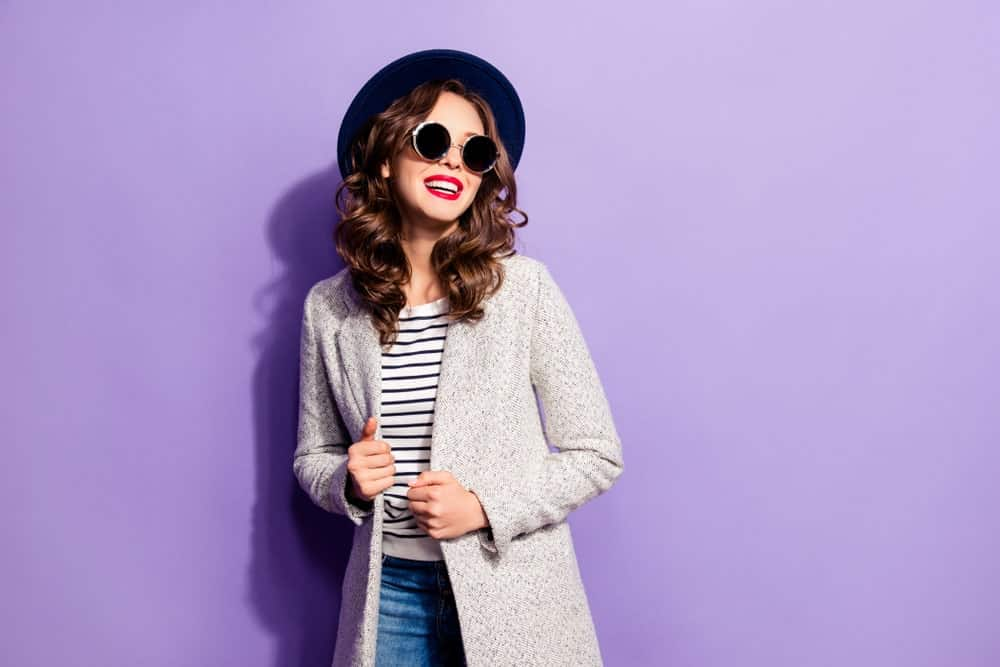 A girl posing in a fashionable outfit with a purple backdrop.