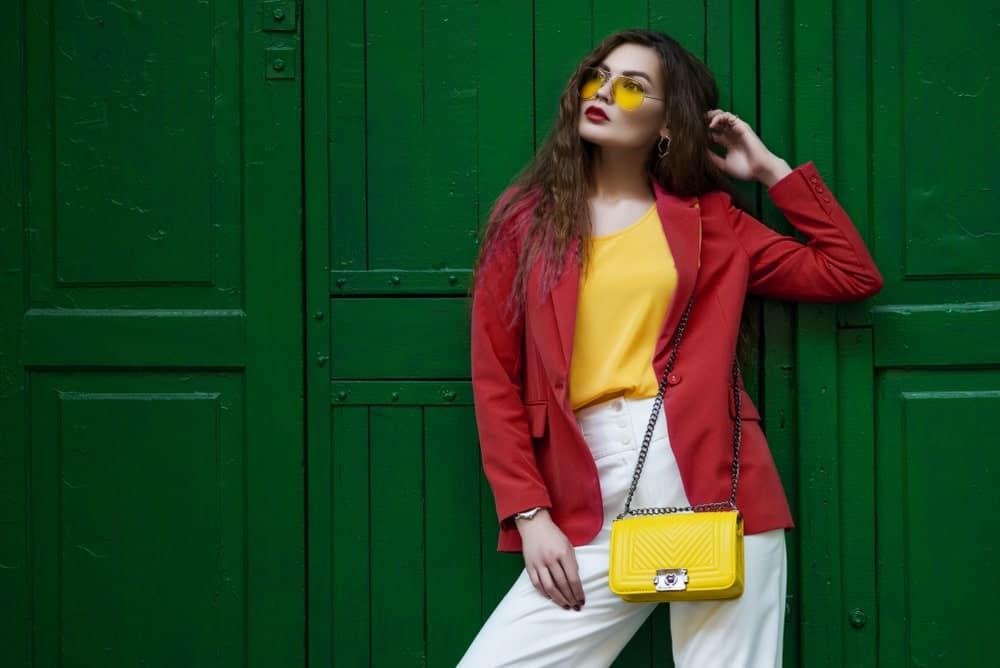 Woman wearing a red blazer and a matching yellow sunglasses, top, and shoulder bag while leaning against a green door.