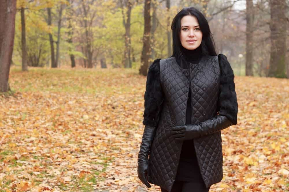 A young, beautiful woman in a quilted black jacket, walking in the autumn park.