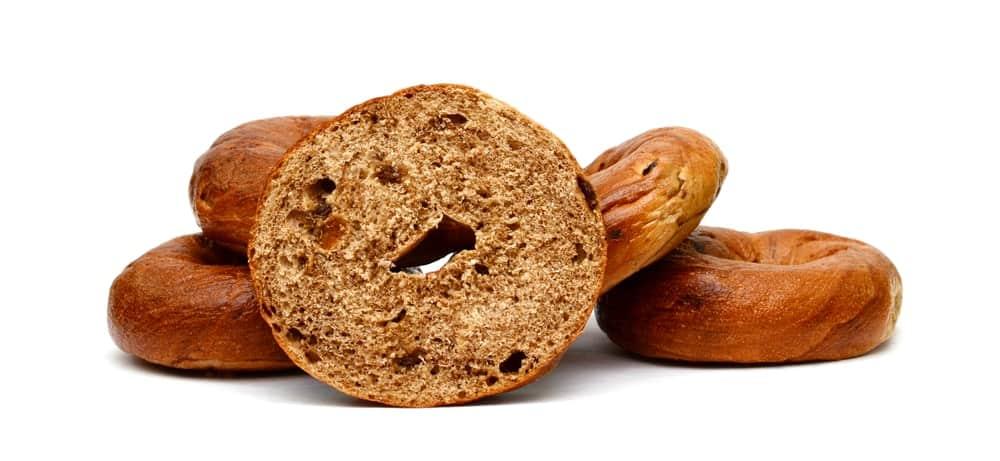 A half cut bagel with cinnamon and raisins