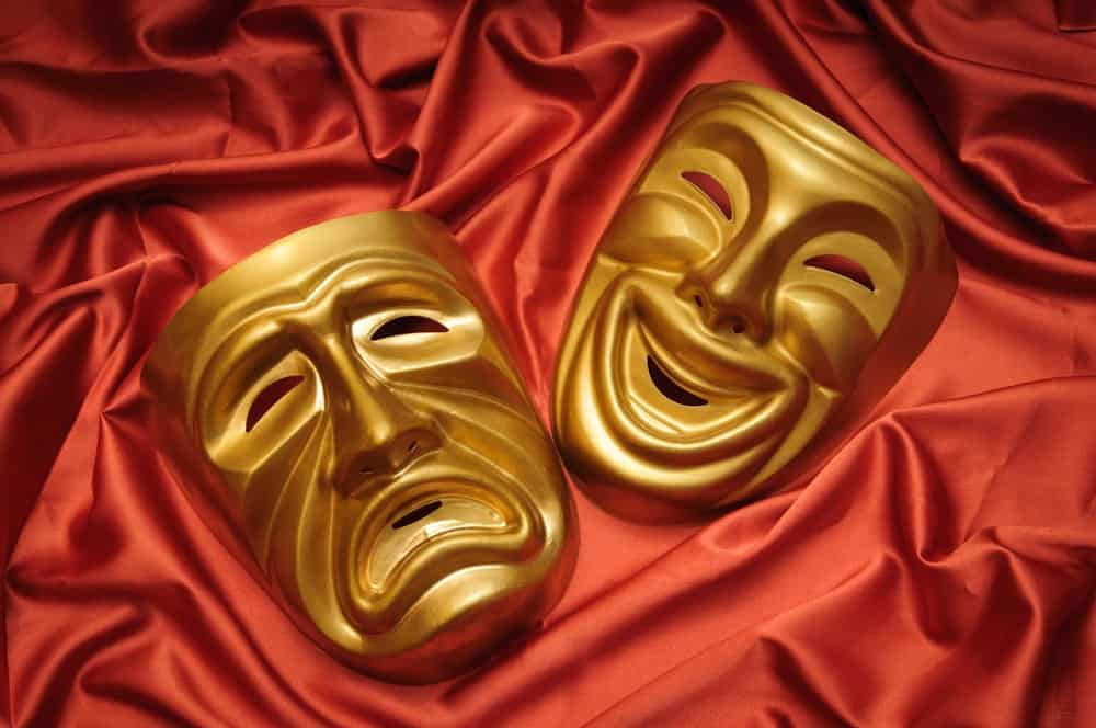 Sad and happy masks on red silk.