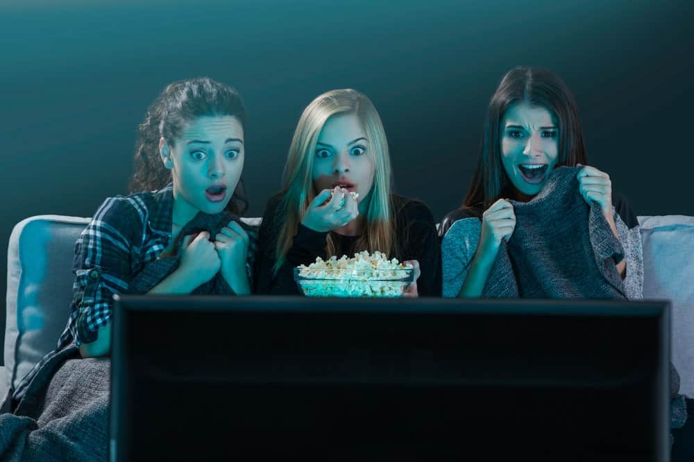 Three teenage women reacting as they watch a horror TV drama.