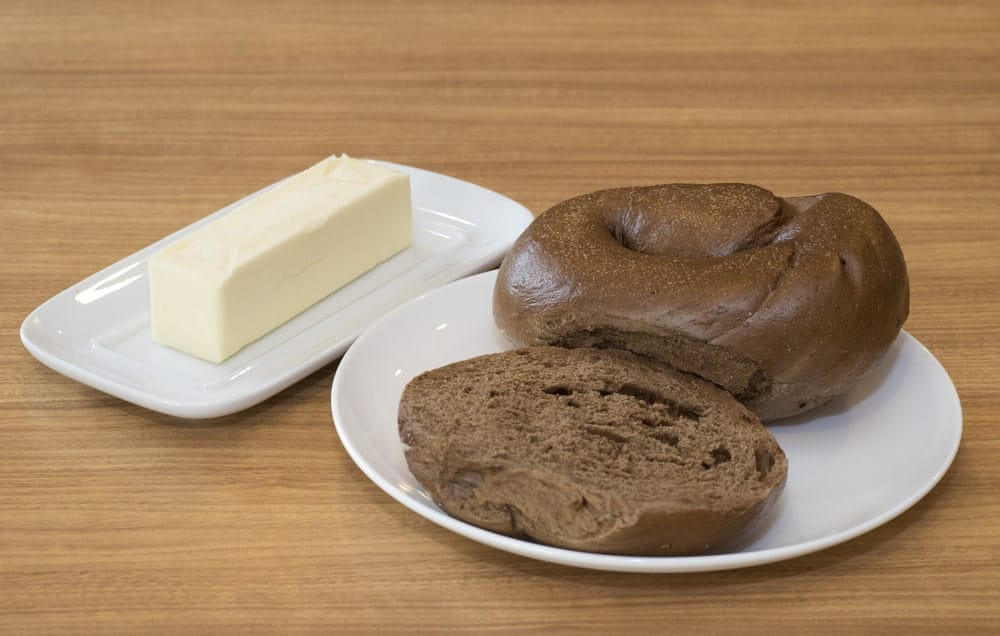 Two Pumpernickel Bagels on a White Plate