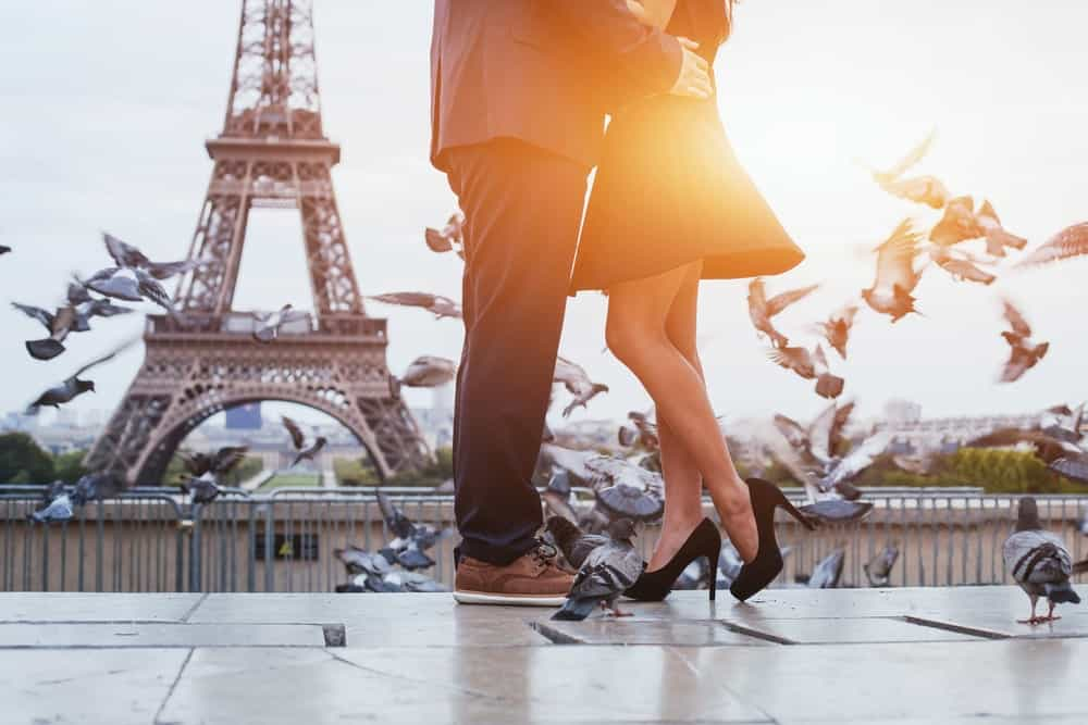 Low shot of a man and woman surrounded by pigeons and with a backdrop of the Eiffel Tower.