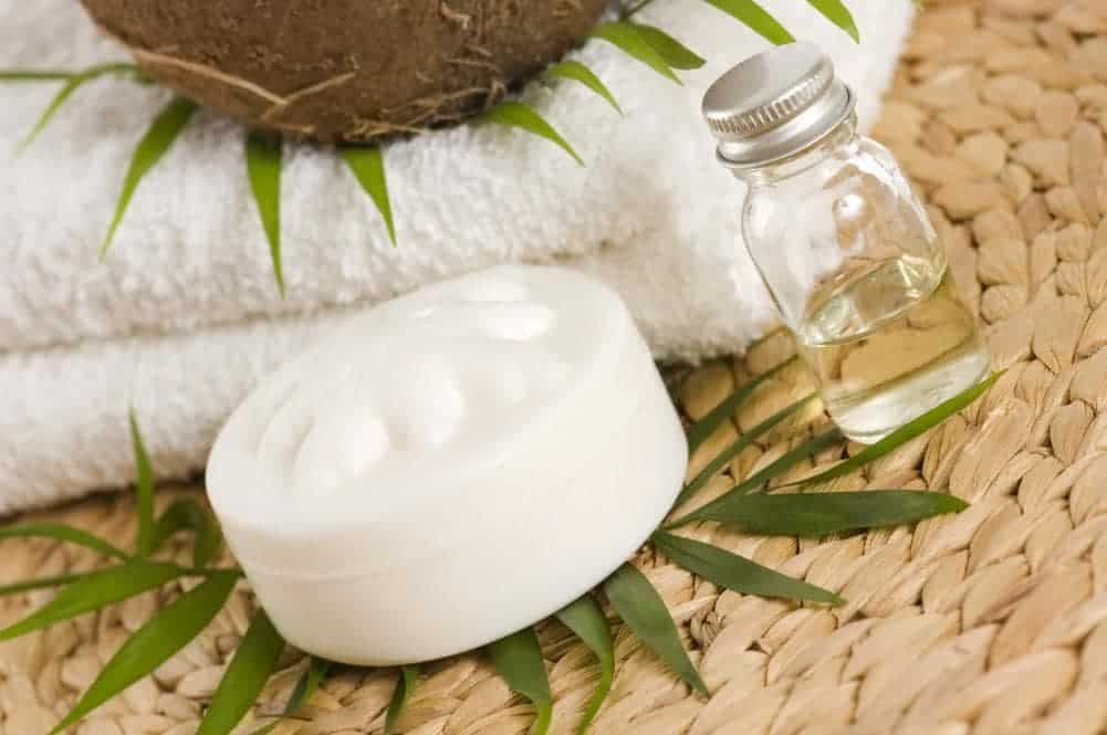 A small bottle of coconut oil beside a white container with leaves and white folded towels.