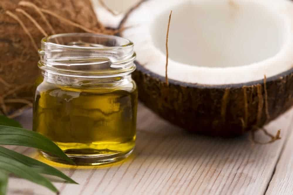 A small jar of coconut oil beside a sliced coconut.