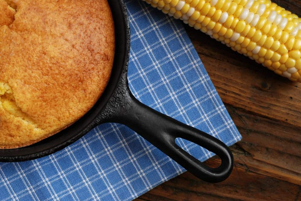 A pan of baked cornbread on a blue checkered placemat beside a corn on a rustic desk.