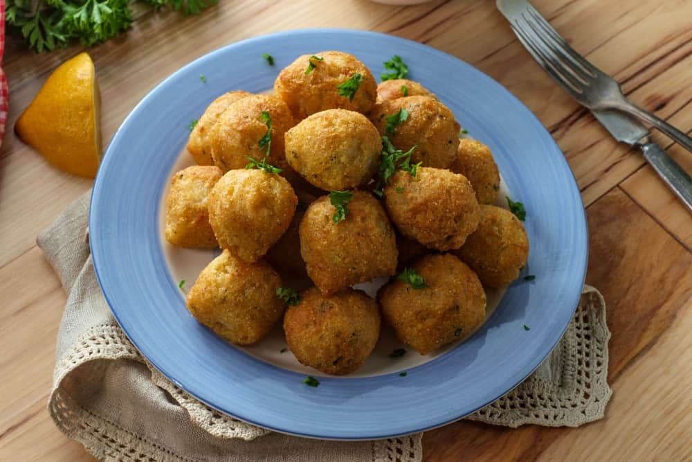 Hushpuppies served on a blue plate.