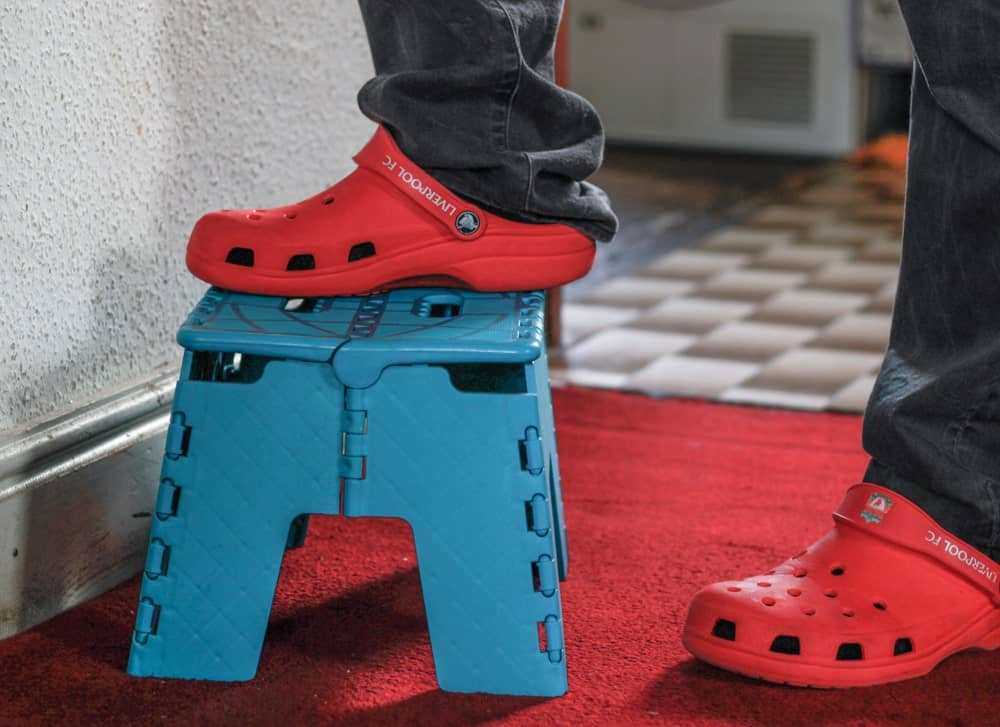 A Man's Foot on a Blue Stool with Crocs on.