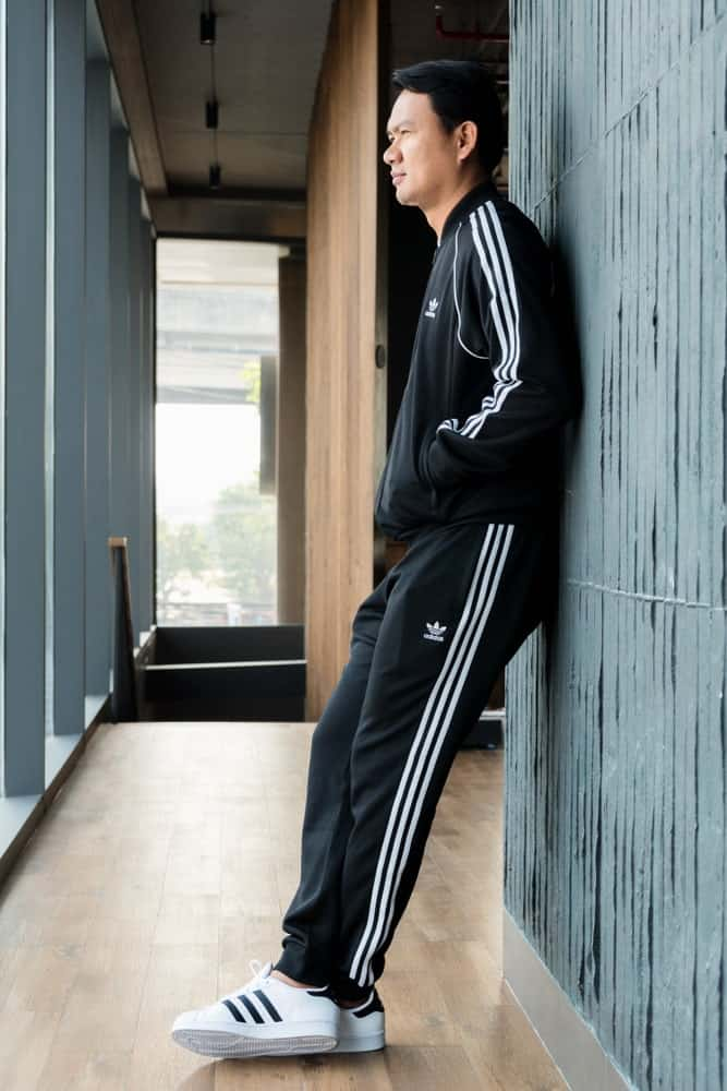A man posing in Adidas striped pants